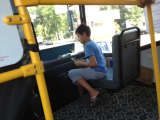 夏休みでお父さんの手伝い?バスで切符を切る少年